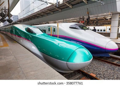 TOKYO - APRIL 1 : Green E5 series and white E2 series bullet trains on April 1 , 2015 in Tokyo.They service as super express (or high-speed train) for Tohoku Shinkansen (Tokyo - Shin Aomori route).