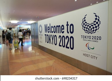 """TOKYO - AUGUST 4, 2017 - Motion blur of tourists past """"Welcome to Tokyo 2020"""" message is seen at the arrival gate in Haneda Airport, Tokyo, Japan."""