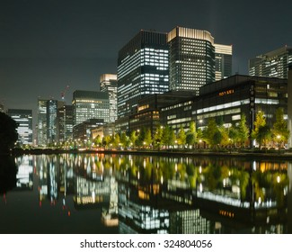 Tokyo business district with tall office buildings and the imperial palace moat at night