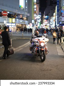 TOKYO - DECEMBER 12 2014 : A big motorcycle is crossing the pedestrain area of shibuya at night, on December 12, 2014 in Tokyo.