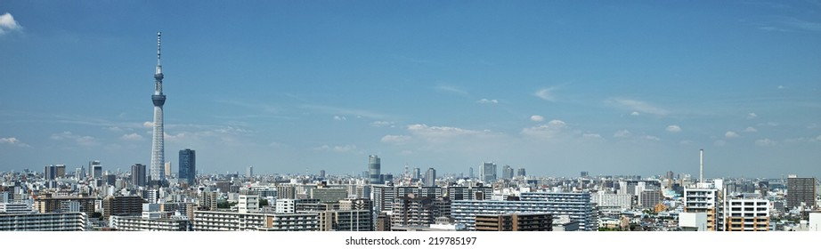 Tokyo downtown skyscrapers with the Skytree on blue sky and white clouds background