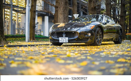 TOKYO - FEB 2, 2015: Maserati GranTurismo in parking lot covered by fallen ginkgo leaves. The GT is a two-door, four-seat coupe produced in Italy since 2007.