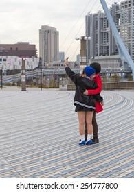 Tokyo - February 7, 2015: Two girls in bright clothes take selfie on the bridge near Odaiba February 7, 2015, Tokyo, Japan