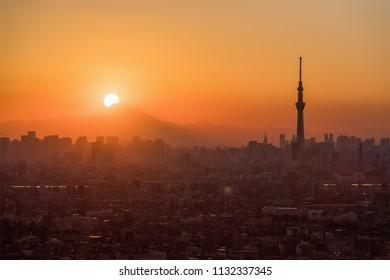 Tokyo Fuji diamond with Tokyo Skytree landmark.  Diamond Fuji is View of the setting sun meeting the summit of Mt. Fuji