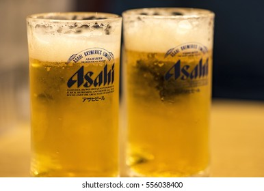 TOKYO - JAN 11: Asahi beer  with foam in a glass on wooden table in Tokyo on January 11. 2017 in Japan