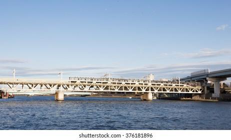 Tokyo - January 28 2015: Railway bridge across the river Sumida and fast train subway rides over the bridge in the evening January 28, 2015, Tokyo, Japan