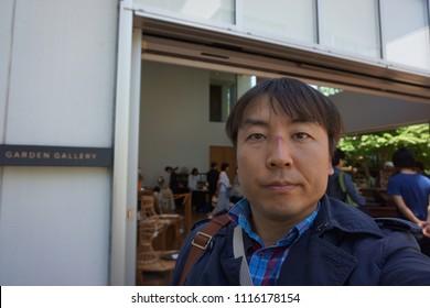 tokyo, japan, 05 08 2017 : a man standing in front of garden gallery antique market at hillside terrace area in daikanyama