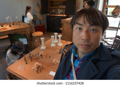 tokyo, japan, 05 08 2017 : a man standing in front of miniature of toy soldiers at garden gallery antique market in hillside terrace area of daikanyama