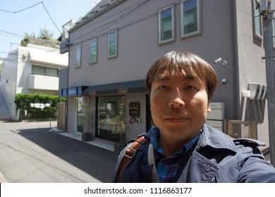 tokyo, japan, 05 08 2017 : a man standing in front of kids wear shop at hillside terrace in daikanyama