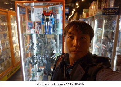 tokyo, japan, 05 08 2017 : a man standing in front of monster and robot toys in mandarake, vendor of used anime and manga related products at shibuya