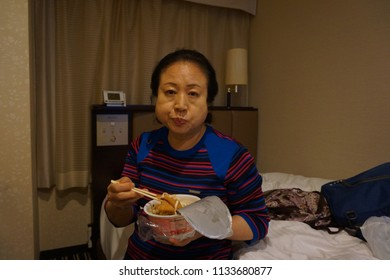 tokyo, japan, 05 08 2017 : a woman eating instant cup noodles in the hotel room at east shinjuku