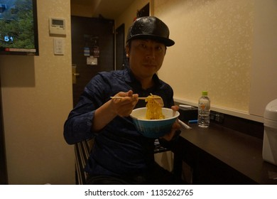 tokyo, japan, 05 08 2017 : a man eating instant cup noodles in the hotel room at east shinjuku