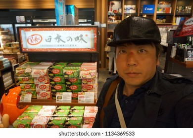 tokyo, japan, 05 09 2017 : a man standing beside display of limited edition of kitkat only in japan at haneda international airport