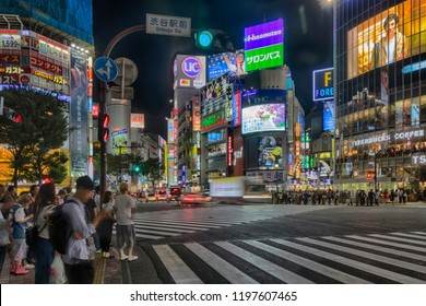 TOKYO, JAPAN - 10 of September 2018: Shibuya crossroads at night, with a lot of displays, neon lights and other advertisement, cars on road and people. Japan sight. HDR image