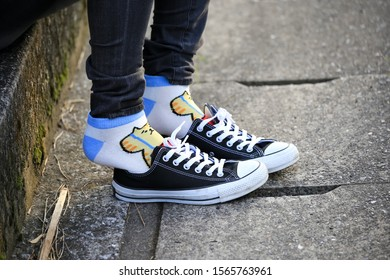 tokyo, japan, 11/18/2019 , detail of the feet of a Woman with childish colorful socks resting her feet out of her shoes.