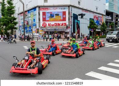 tokyo, japan. 13th august, 2018: cosplayers driving mario karts at tokyo streets