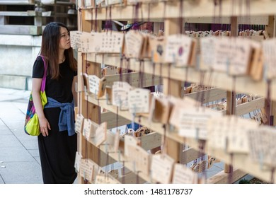 Tokyo, Japan - 14 June 2015 - An Asian woman looks at the ema tablets, Japanese wooden wishing board, hanging on racks at temple in Tokyo, Japan on June 14, 2015