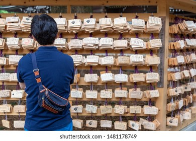 Tokyo, Japan - 14 June 2015 - An Asian man looks at the ema tablets, Japanese wooden wishing board, hanging on racks at temple in Tokyo, Japan on June 14, 2015
