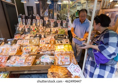 TOKYO, JAPAN - 18 JULY 2016 - Seafood snack vendor shows his customer the price in his shop in Tsukiji Fish Market, Tokyo, Japan on July 18, 2016.