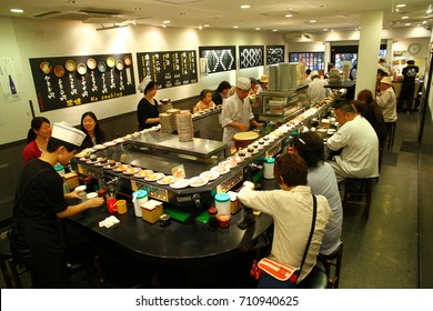 TOKYO, JAPAN - 19 May 2013. A running sushi restaurant from Asakusa. Sushi plates are running on the conveyor band and people can pick the one they like to eat.