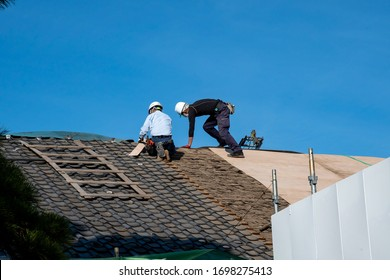 Tokyo, Japan - 19th February, 2020: Men at work replacing shingles on the roof of a building.