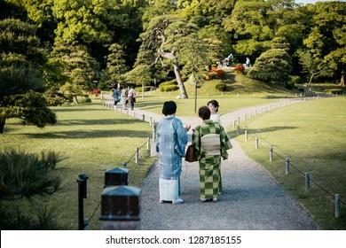 TOKYO, JAPAN - 20 APRIL, 2018: Women wearing traditional japanese kimonos walk along the Hamarikyu Garden in Tokyo, Japan.