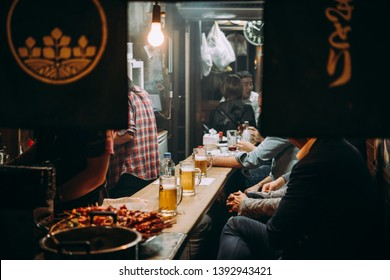 TOKYO, JAPAN - 20 APRIL, 2018: People enjoy evening drinks at one of the food stalls in the streets of Shinjuku district in Tokyo, Japan.