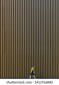 Tokyo, Japan - 2017 November 3rd: In the afternoon, a receptionist hostess walking along the huge architectural wall in the Tokyo International Forum.