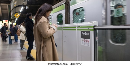 TOKYO, JAPAN - 23RD DECEMBER, 2017. Commuter waiting for a train at Japan Railway Ebisu Station platform.