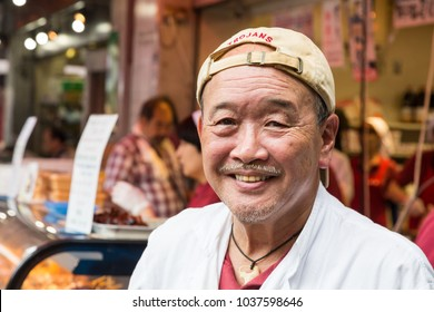 Tokyo, Japan - 24 June 2016: Cheerful street vendor  at a stall in Tsukiji street market in Tokyo. This is the biggest fish market in the world.