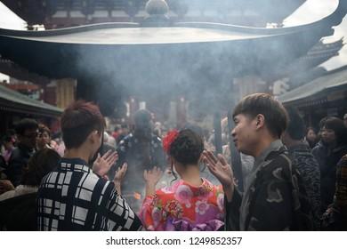 TOKYO, JAPAN - 24 November 2018:  Tourists are smoke bathing. Shintos believe that bathing incense smoke make them lucky.