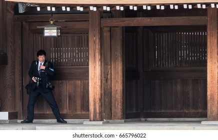 TOKYO, JAPAN - 25TH JUNE 2017. Japanese wedding photogrpher at Meiji Jingu temple. The shrine is a popular site for marriage ceremonies and on busy weekends, it carries out around 15 weddings a day.