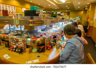 TOKYO, JAPAN -28 JUN 2017: Unidentified people eating an assorted japanesse food over a table, inside of a kaitenzushi conveyor belt sushi restaurant. Consumers pile up colored empty plates when they