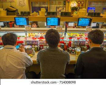 TOKYO, JAPAN -28 JUN 2017: Unidentified people eating an assorted japanesse food over a table, inside of a kaitenzushi conveyor belt sushi restaurant, in Tokyo