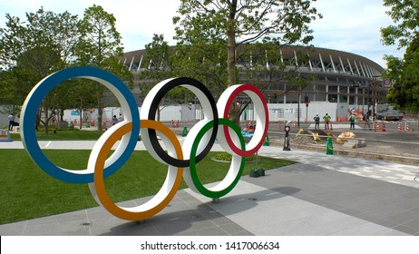 TOKYO, JAPAN - 4 JUNE 2019 : The five ring symbol of the Olympic Games and view of the New National Stadium under construction for Tokyo Olympic 2020.
