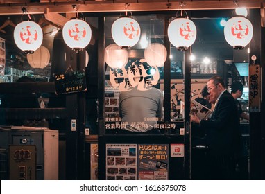 TOKYO, JAPAN - APR 11,2019 People drinking in Bar beer Local restaurant Japanese Salaryman Tokyo city Japan nightlife