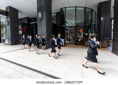 Tokyo, Japan - April 1, 2019: Kyobashi Edogrand modern business center building with architecture entrance and many young women businesswomen walking from conference