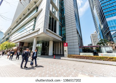 Tokyo, Japan - April 1, 2019: Road street with sign for JP Morgan bank and Mitsubishi electric corporation with Japanese group of business people on conference in downtown