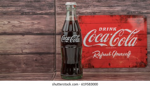TOKYO, JAPAN - APRIL 10TH, 2017. Coca Cola original taste drinks and vintage metal sign over wooden background., The carbonated soft drink is produced by The Coca-Cola Company.