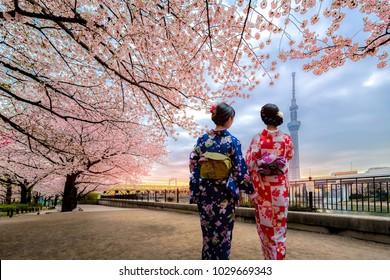Tokyo, Japan - April 12, 2017:  Young women wearing traditional Japanese Kimono and Tokyo Skytree in public park at Sumida River near Asakusa, Tokyo