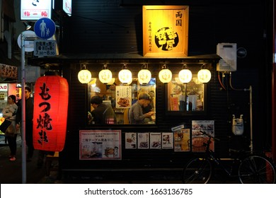 Tokyo, Japan - April 13 2018 : A japanese food stall as seen from outside, with red lanterns at night. People are having dinner inside