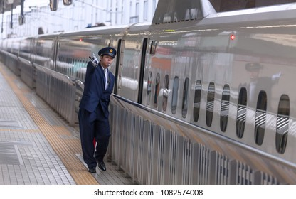 TOKYO / JAPAN - APRIL 14th 2009: Bullet Train Shinkansen in Tokyo station with a conductor signaling the imminent departure to the train driver.