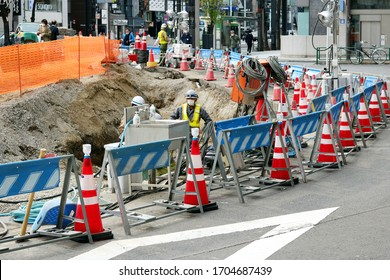 TOKYO, JAPAN - April 15, 2020: Road works being undertaken in Tokyo's Ginza area. People wear face masks during coronavirus outbreak. The site also has a sink & soap for workers to clean their hands.