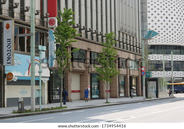 TOKYO, JAPAN - April 16, 2020: People wearing face masks on an almost empty street in Ginza with stores, including Mitsukoshi Department Store, closed during the coronavirus outbreak.