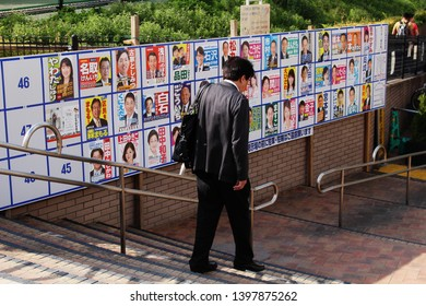 TOKYO, JAPAN - April 18, 2019: A man walks past a noticeboard in a park in Tokyo's Bunkyo Ward with posters of candidates standing in local elections for the local assembly.