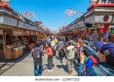 Tokyo, Japan - April 19, 2017: crowd of people in spring sakura on Nakamise Dori, street with food and souvenirs shops, connetting the Kaminarimon Gate at the entrance of Senso-ji Buddhist Temple.