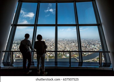 Tokyo, Japan - April 19, 2017: couple of tourists at Tembo Deck observation deck. The Tokyo Skytree is a television broadcasting tower and landmark of Tokyo. Concept of travel and asian metropolis.