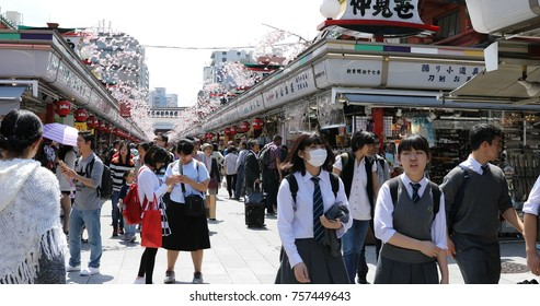 Tokyo, Japan - April 19, 2017: crowd of people in spring sakura on Nakamise-dori, street with food and souvenirs shops, connetting the Kaminarimon Gate at the entrance of Senso-ji Buddhist Temple.