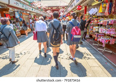Tokyo, Japan - April 19, 2017: people in school uniforms walking on Nakamise Dori, street with food and souvenirs shops. Kaminarimon Gate of Senso-ji Buddhist Temple, Asakusa, on background.