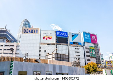 Tokyo, Japan - April 2, 2019: Shinjuku colorful cityscape during day with signs for Odakyu mall and shops stores